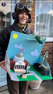 Picture of a child dressed at a pilot hold their school project