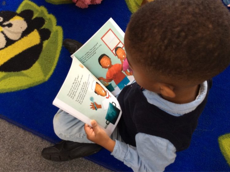 Picture of a child sitting on the carpet, reading a book