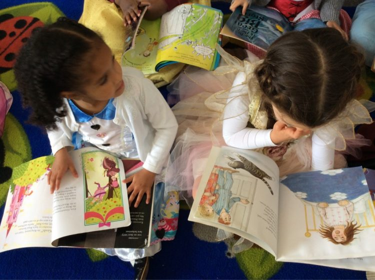 Two children sitting on the carpet reading their books